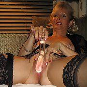 Mature lady masturbating with glass dildo and bottle